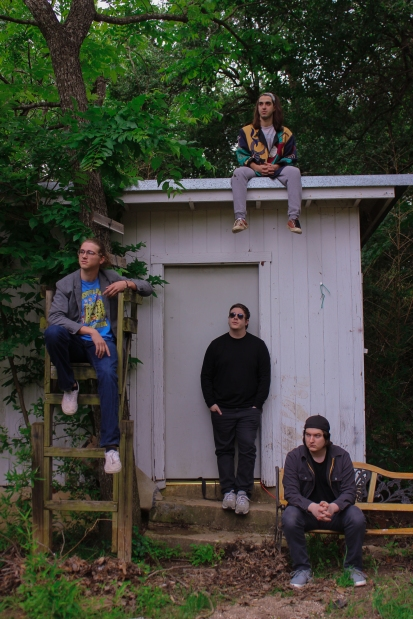 The band sits outside the shack where they recorded their first EP.
