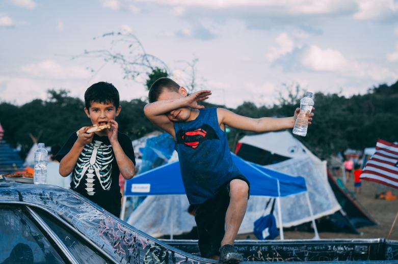 I catch these little boys off guard as they climb on top of a chalked-out car parked in the middle of the festival ground. They catch me more off guard by dabbing.