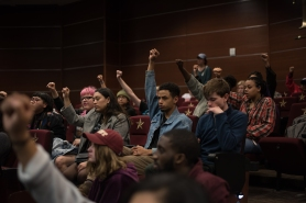 Students raise their fists in solidarity as the national anthem is played at the beginning of the Student Government meeting.