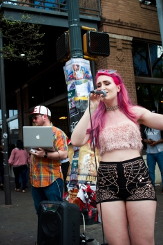 As people walk by, Crystal Clayton grabs their attention with her hot pink hair and electronic-infused R&B sound.