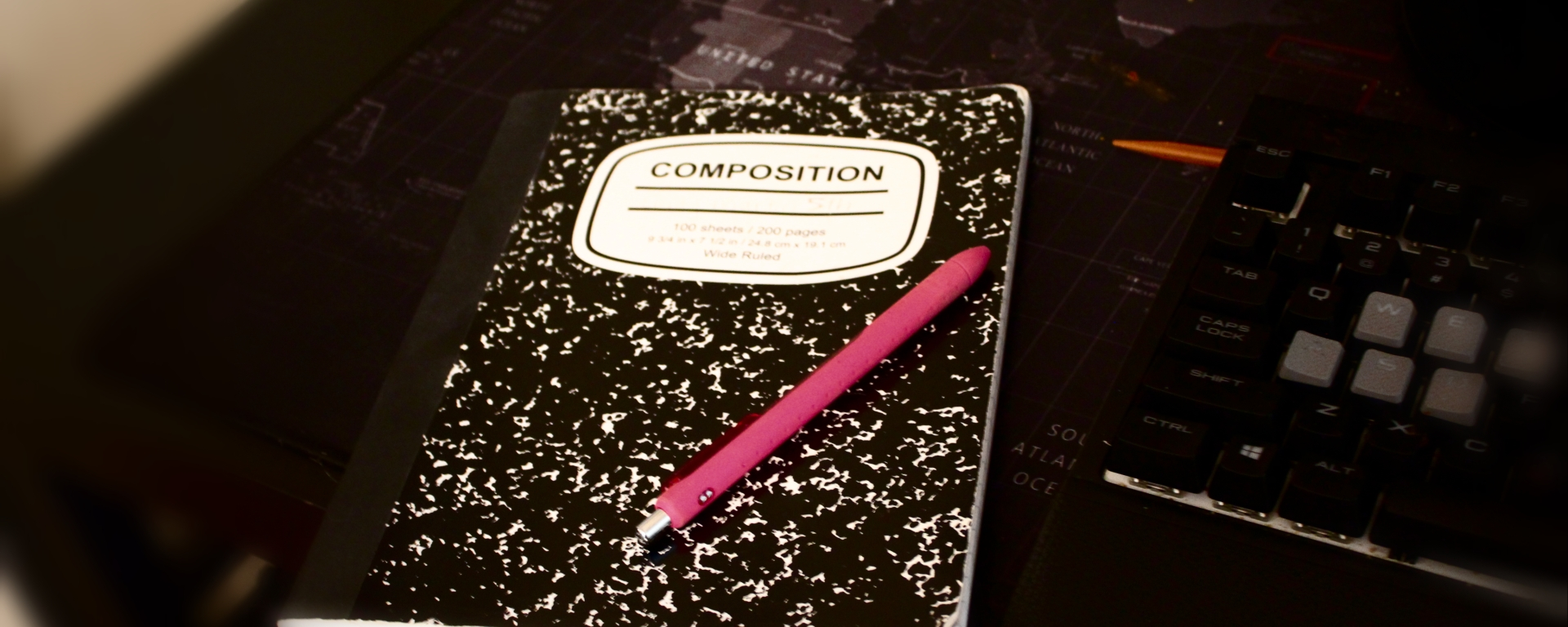 A composition notebook and pink pen next to a keyboard.