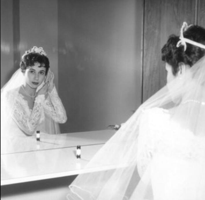A black and white photo of a woman in a wedding gown looking in a mirror.