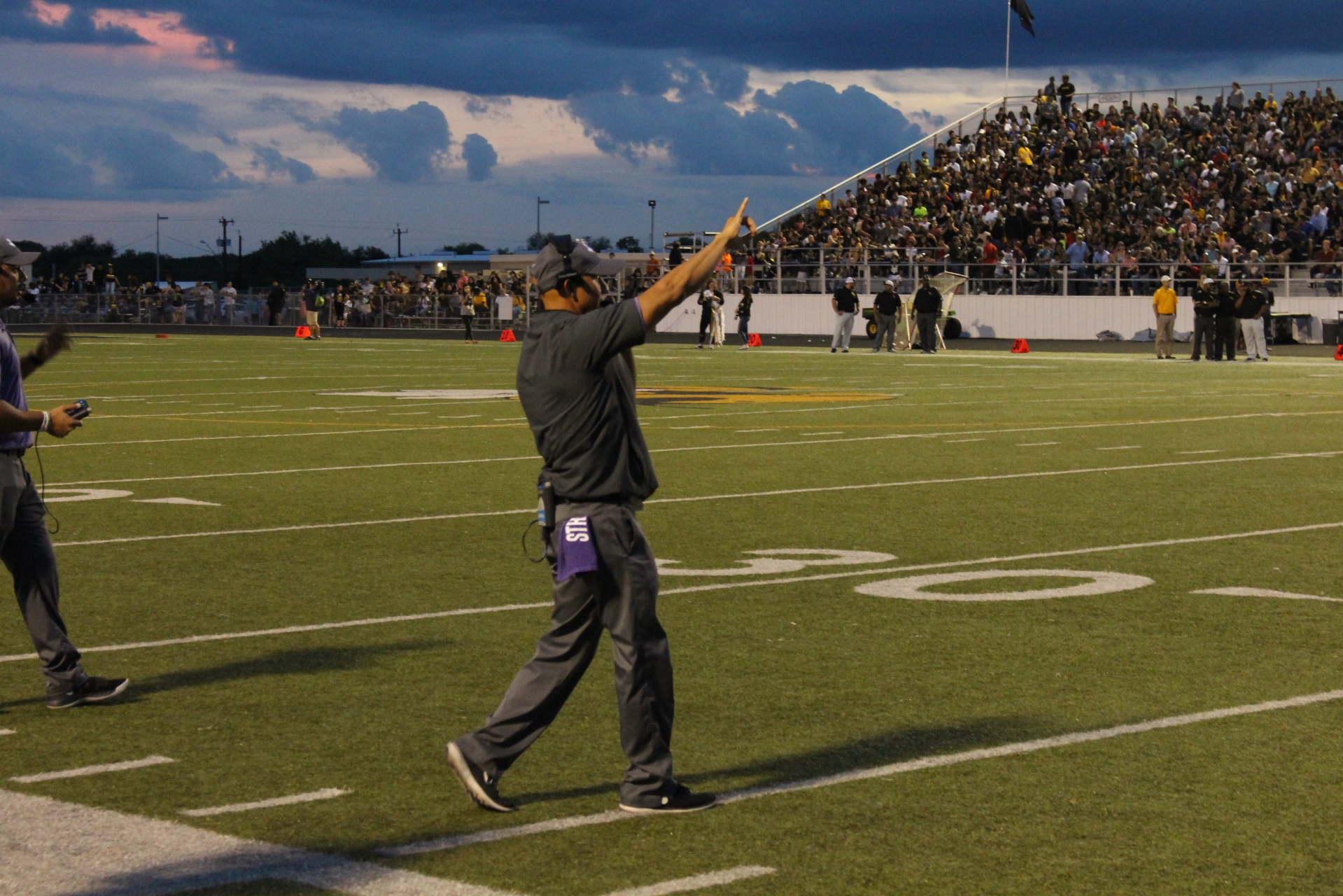 A man making a call at a high school football game.