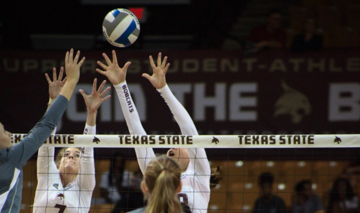 Two Bobcat senior middle blockers cut off the attack by a Roadrunner weak side hitter.