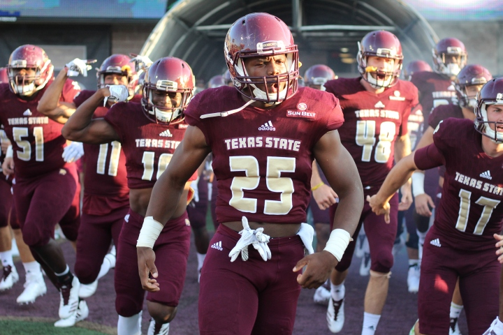 In all black uniforms with golden numbers, the Texas State Bobcats take the field, lead by running back Anthony D. Taylor. Taylor's shouting facial expression and flexed arms reveal the fiery personality and dedication he has to football; traits which have made him a major offensive asset.