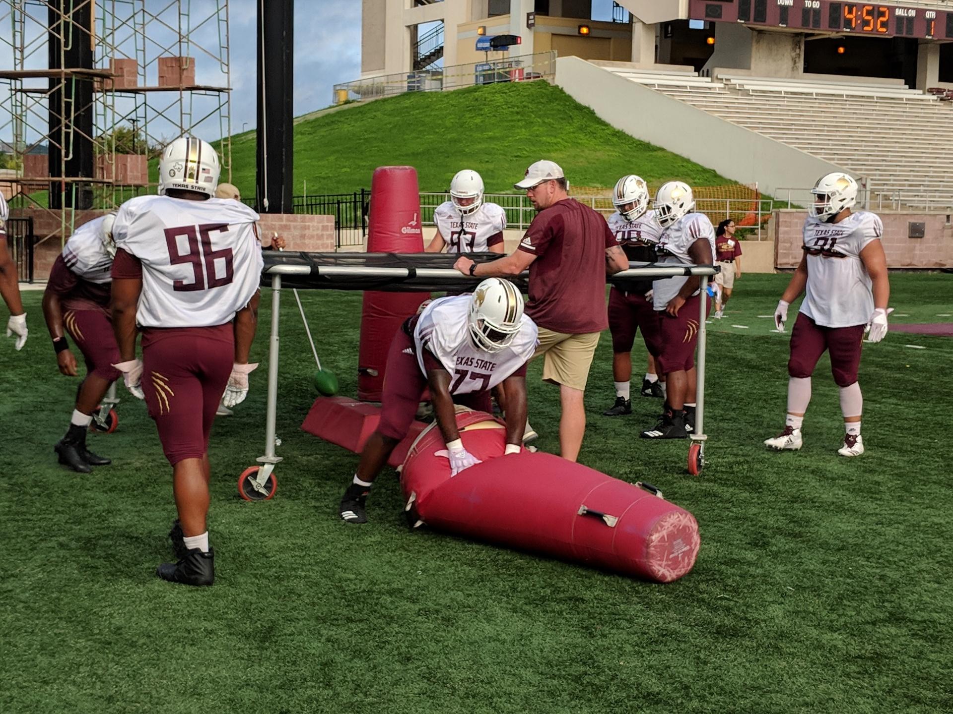 The Bobcat defensive line tackling dummies.