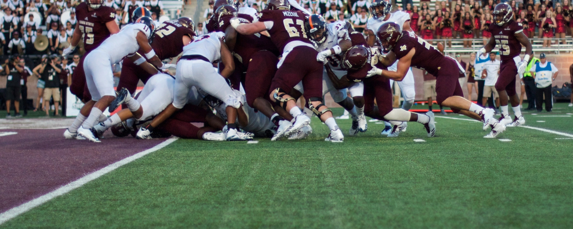 In a goal line scrum of white UTSA jerseys and black Texas State jerseys, the Texas State offensive line is creating a push into the end zone for their running back.