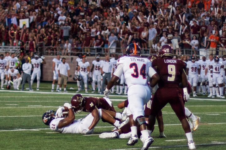 In all black uniforms, a Texas State linebacker has forced a UTSA running back to the ground as linebacker Bryan Londoncreeps up to assist if needed.