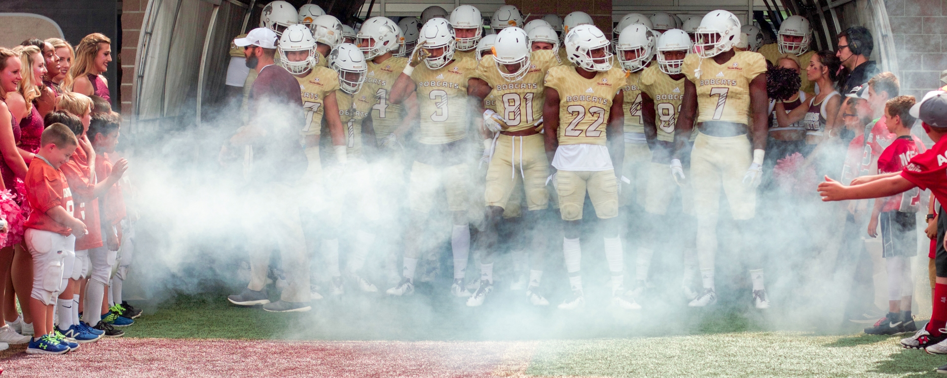 In their bright golden jerseys, the Texas State Bobcat Football team prepares to rush out of a smoke-filled tunnel to an enthusiastic home crowd. Some players look at each other, others look down, but all have rigid bodies from the tense of the situation, waiting to pour their exuberance onto the field of play.