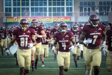 Texas State football players running onto field