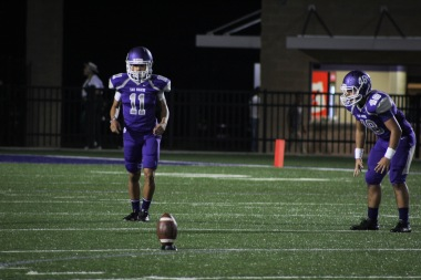 The senior kicker for San Marcos High School charging forward to kick the football.