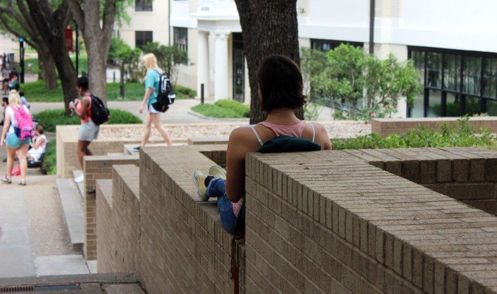 An image of a young woman from behind sitting on a brick ledge on the Quad at Texas State.