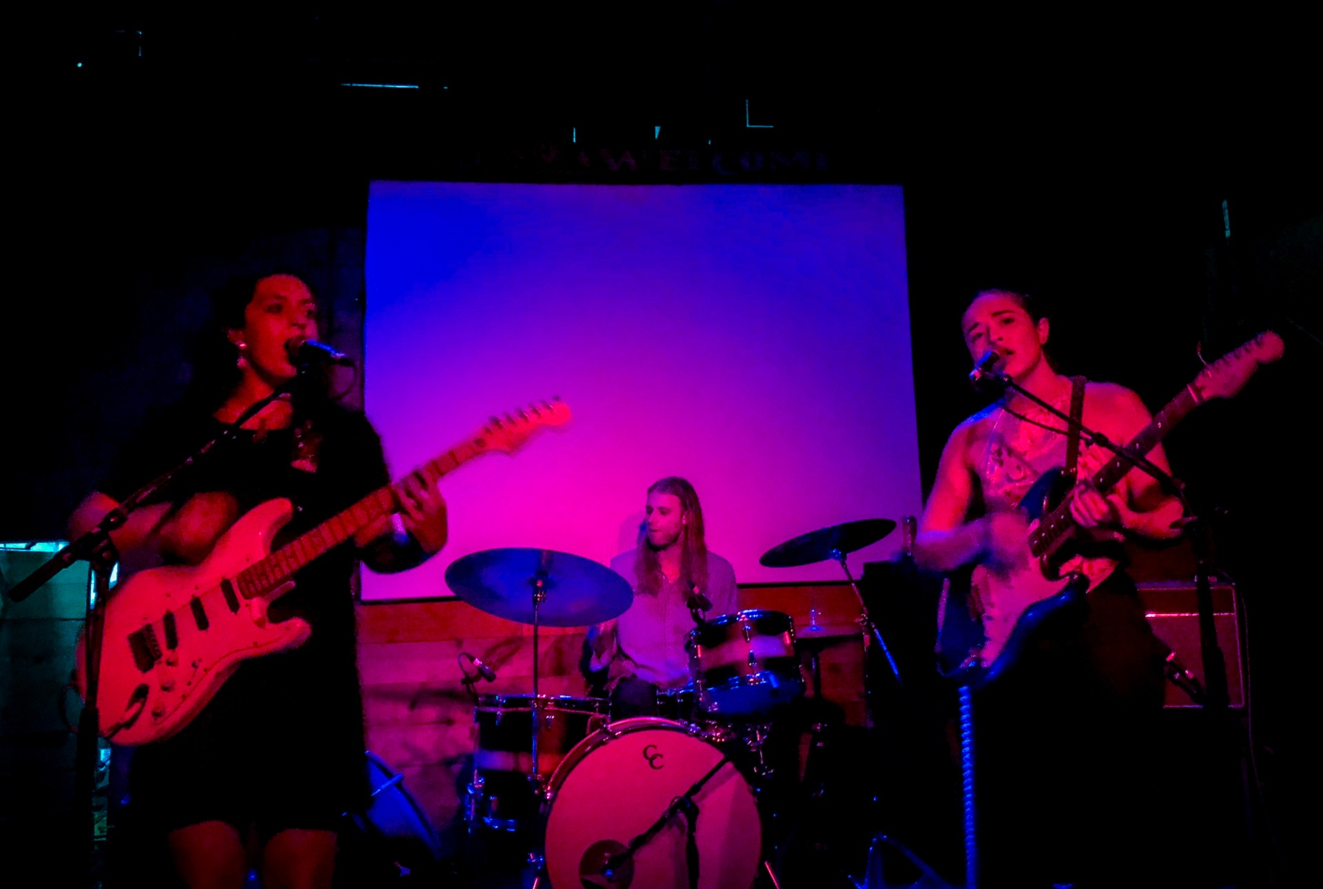 The band on a small stage with two guitarists in the foreground and a drummer behind them.