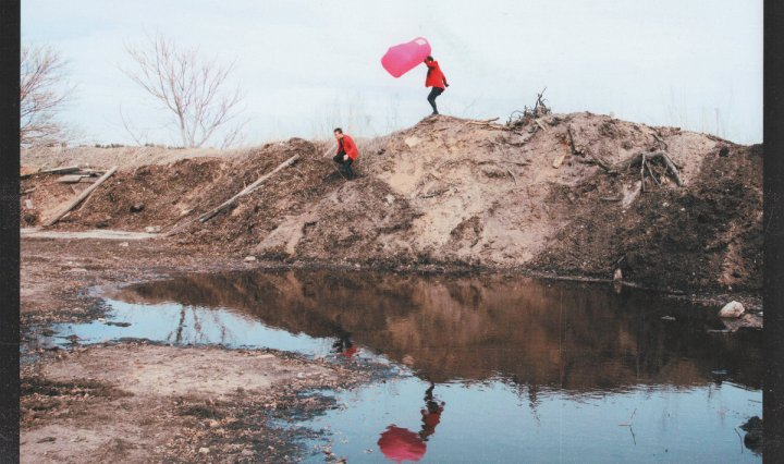 Two people in red coats at a creek, one of them is holding a bright pink cloth.