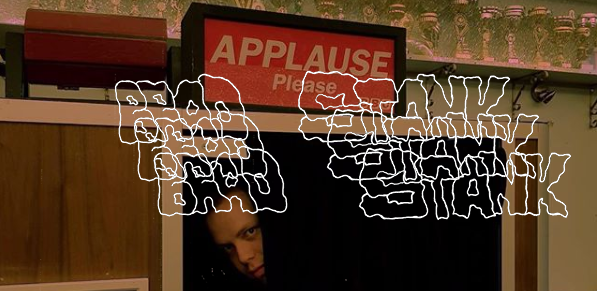 "Brad Stank poses for a photograph underneath a sign that reads ""Applause Please."" The words ""Brad Stank"" appear in triplicate in the foreground of the picture."