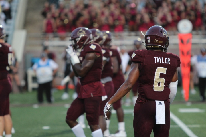 In black jerseys, Anthony J. Taylor and several other members of the Texas State special teams look toward the sideline to eagerly listen to final coaching instructions. Taylor has been a defensive member always eager to win, prepare, and listen, hence a slow crafting which has created exhilarating pass defense and his first career interception.
