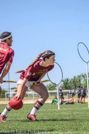 Female quidditch player reaching for dodgeball on Quidditch field