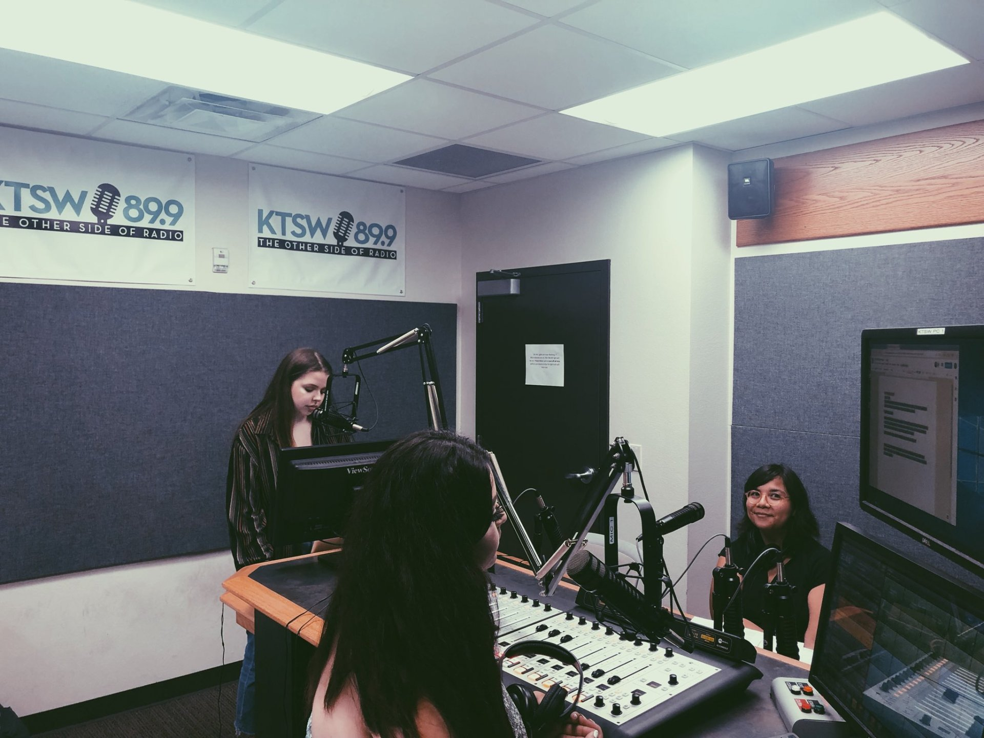 Three young women in the KTSW studio. One is smiling.