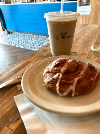 Iced coffee and a cinnamon roll on a table.