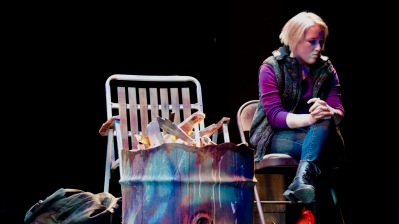 Payton Mayfield sits alone by a fire pit in the dress rehearsal of Mr. Burns.