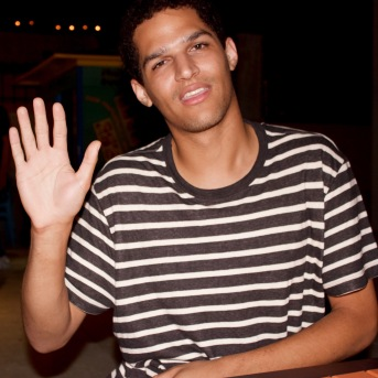 Eric Ross waving hello while sitting at a bench.