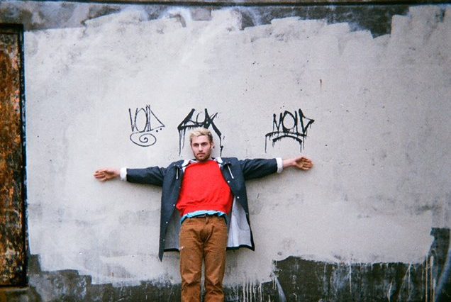 Yoke Lore standing in front of a building wall with graffiti tags above him
