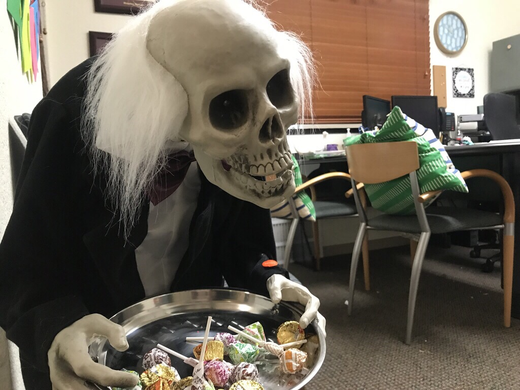 A creepy halloween candy holder of an butler who is also a skeleton