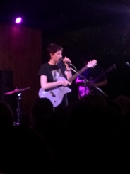 Greta Kline of Frankie Cosmos grabbing the mic on stage