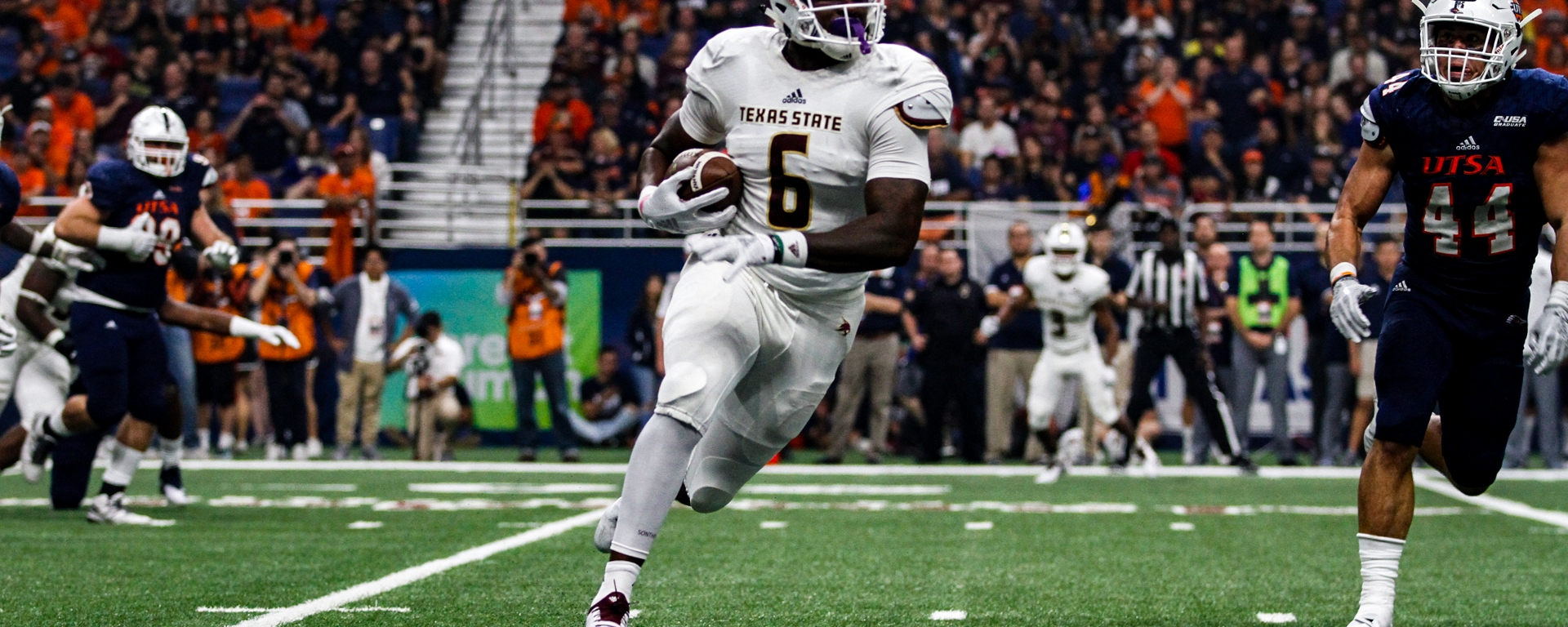 Number six, Tight End Keenen Brown, in all white and chased by two blue-uniformed UTSA defenders, powers down the field after catching a pass against UTSA earlier this season. His dynamic balance of power in running style and athleticism in route running has added explosiveness to the Texas State offense.