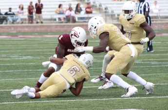 In golden jerseys, a reflection of the incurring play, number six, cornerback Anthony J. Taylor, number seven, linebacker Kumonde Hines, and number 18, linebacker Frankie Griffin all break into the backfield, bringing a ULM running back to the ground early in the playset.