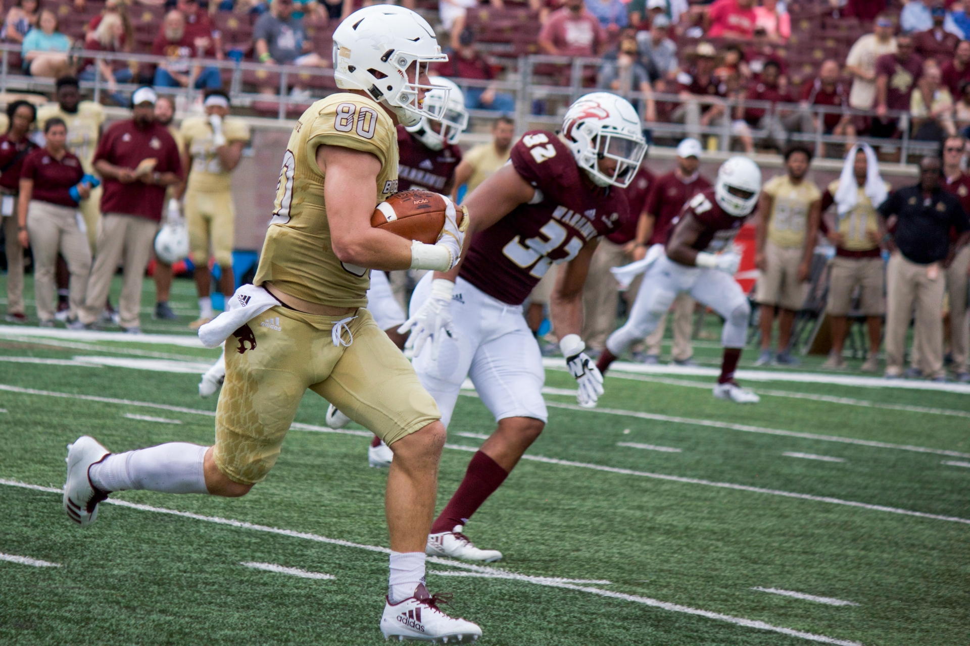 After hauling in a pass, wide receiver number 80 Hutch White strides downfield in the Bobcats' golden uniforms as number 32 of ULM, in a dark black jersey, begins to chase him. The offensive identity was a major portion of coach Withers' dialogue on Monday. Wide receiver Hutch White has shown the ability to be a major part of the positive, passing plays coach is looking for