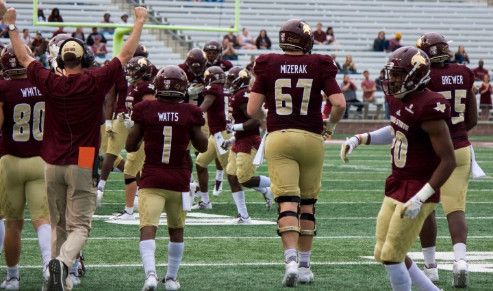 From left to right, Hutch White – number 80 -, Tyler Watts – number one -, Tryston Mizerak – number 67 - , Stephan Johnson – number 20 - , and Aaron Brewer – number 55 - celebrate as Texas State obtains the ball after a turnover. The offense capitalizing off turnovers (14 points on Saturday) has been a consistent theme throughout Coach Withers' tenure as head coach. In the background, the defense can be seen gathering around number two, linebacker Gabe Lloyd, who has obtained the turnover.