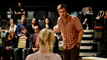 Jessica in pink and Jack in plaid confronting each other during rehearsal.