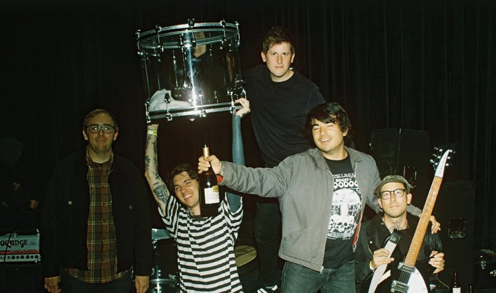 The band members, one holding up a drum, and their gear on a black background.