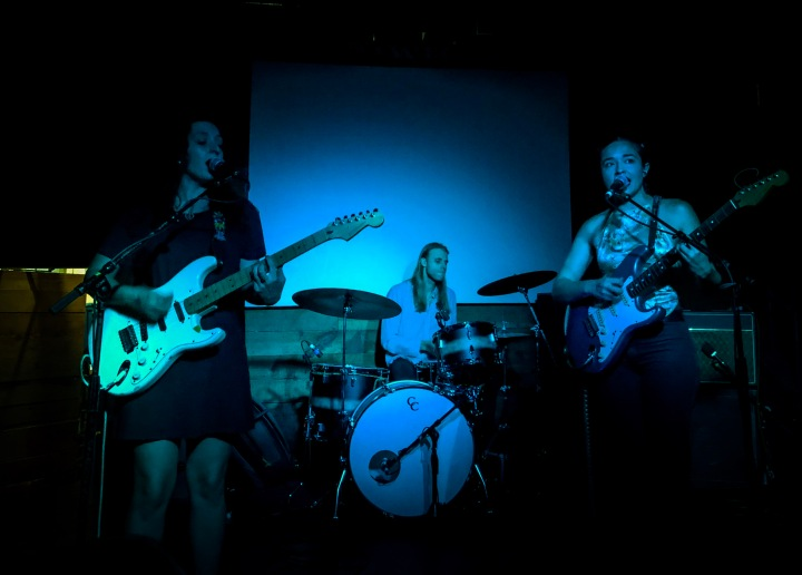 The band, Ohmme, performing on the small indoor stage of Mohawk Austin, their two electric guitarists and vocalists in the foreground and their live drummer in the background.
