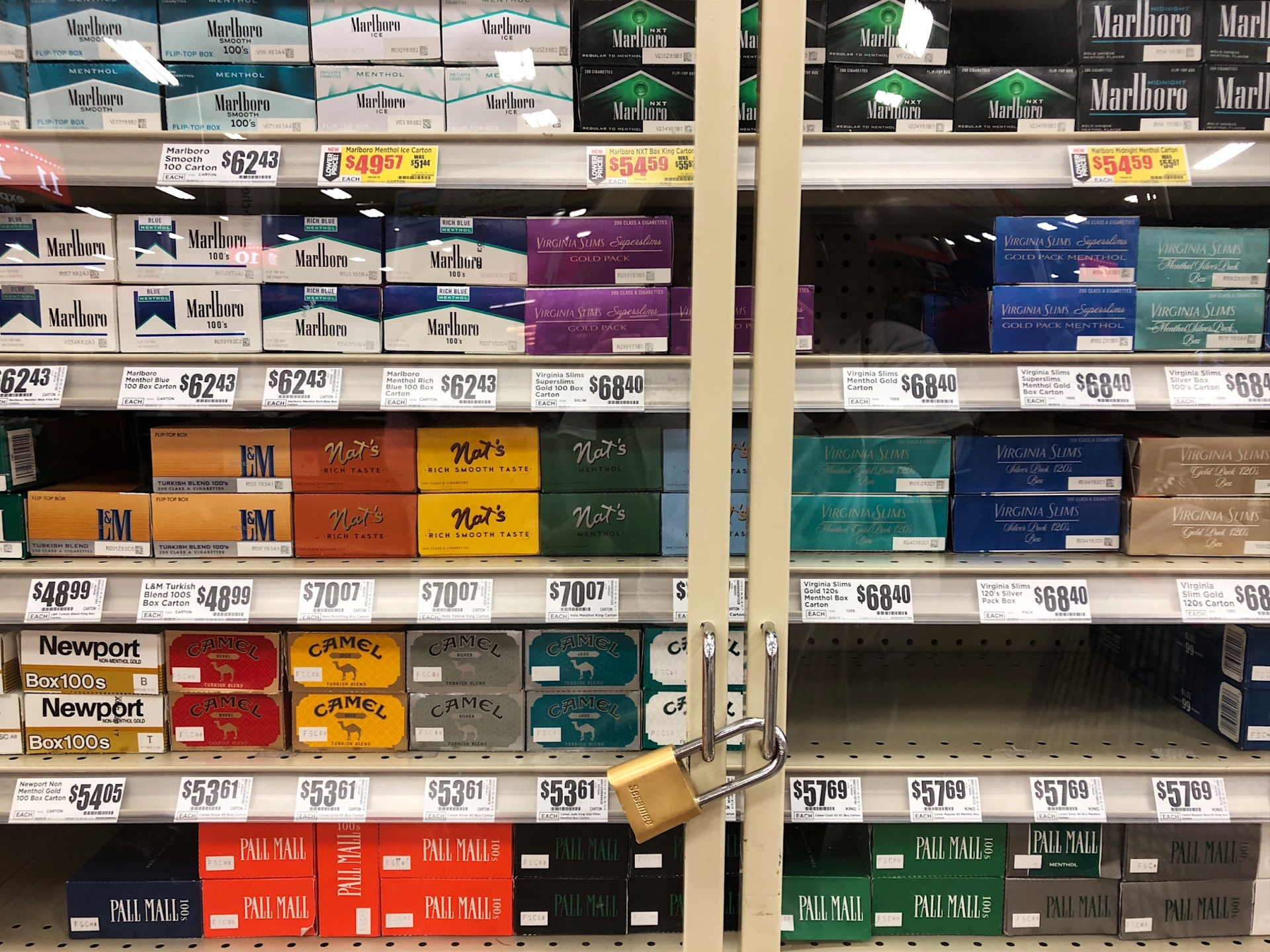 Multiple shelves of tobacco products (such as cigarettes) enclosed within a glass casing.
