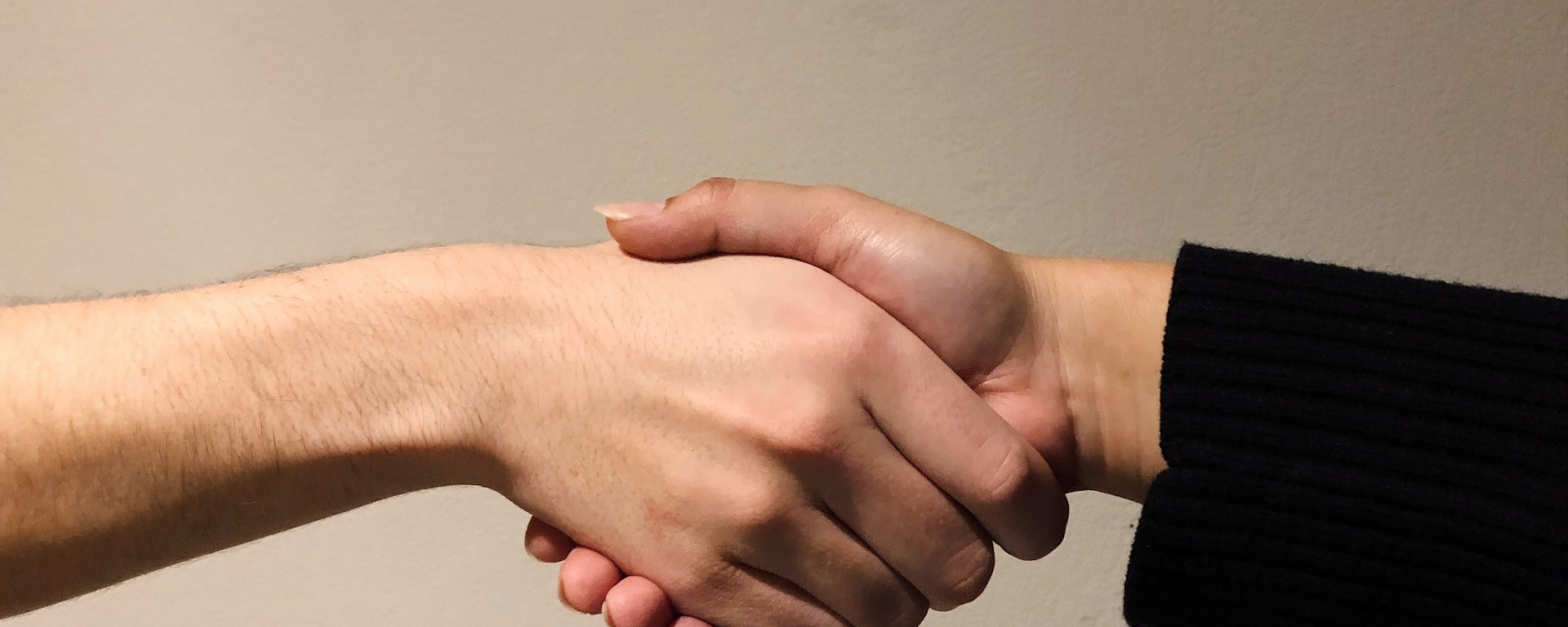 The photo features two hands in a handshake position in front of an ivory-colored wall.