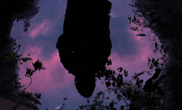 A reflection in a small puddle of water of a person with a vibrant sky in the background.