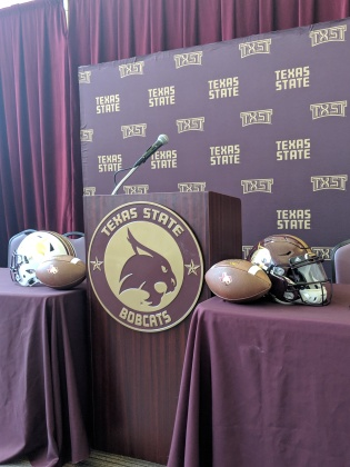 Encased by a white Bobcat helmet to the left and a black Bobcat helmet to the right, with footballs on either side