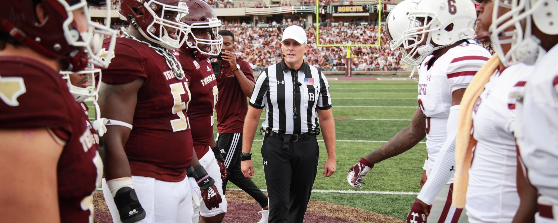 Referee between two opposing college football teams.