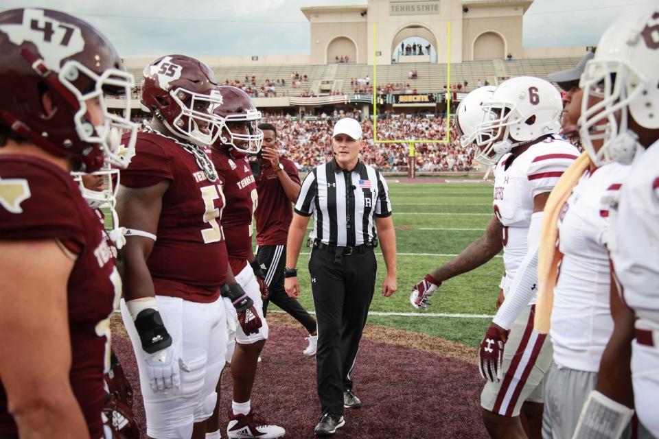 Referee between two opposing college football teams.