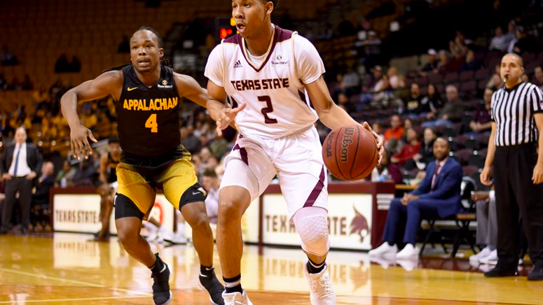 A Texas State player bounds ahead of an Appalachian State player.