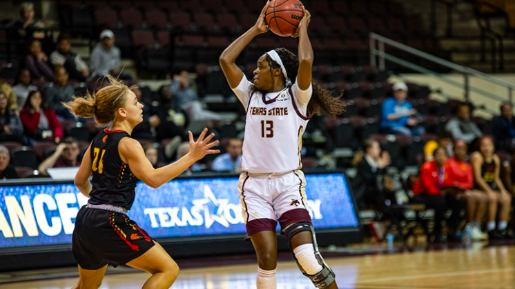 A Texas State player goes to shoot over an opponent's head.