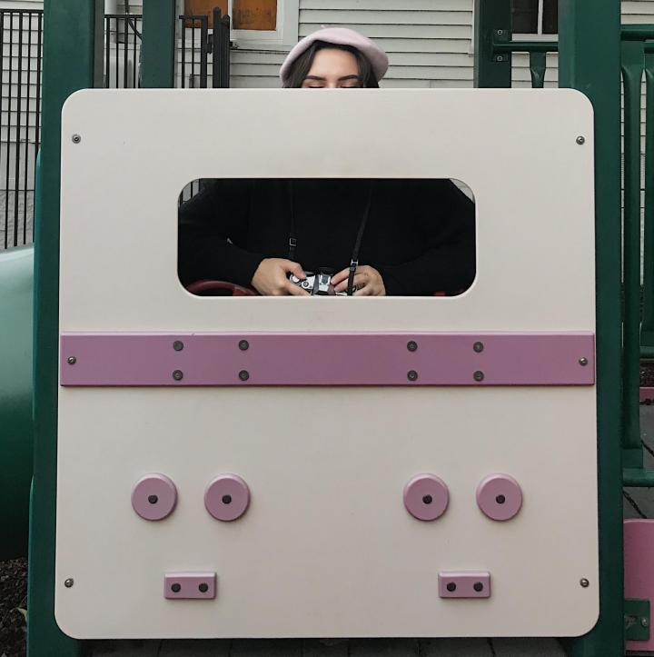A girl holding a camera, sitting in a playhouse