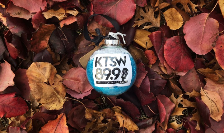 The photo features a clear ornament with sea blue tissue paper on the inside as well as a paper with the KTSW logo printed on it (KTSW 89.9: The Other Side of Radio). The ornament was photographed on a pile of fallen red, brown and yellow leaves.