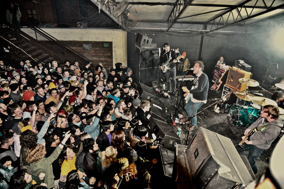 Jeff Rosenstock on stage with his band pictured on the right playing to a densely packed pictured on the left.