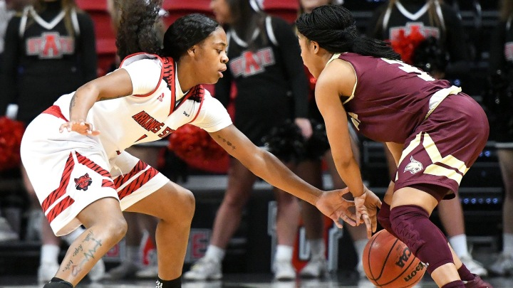A Texas State player keeps the ball from an Arkansas State player.