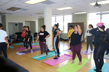 A group of women stand on yoga mats in a room, all wearing activewear as they wait to start the session.