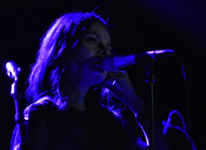 A woman singing into the microphone with blue light behind her.