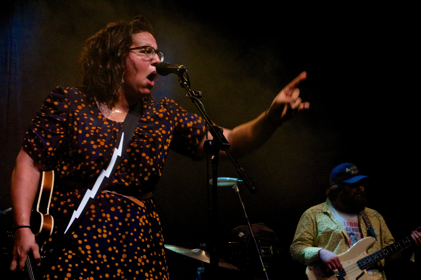 A woman with glasses and a blue and yellow dress sings loudly and gestures while holding a guitar.